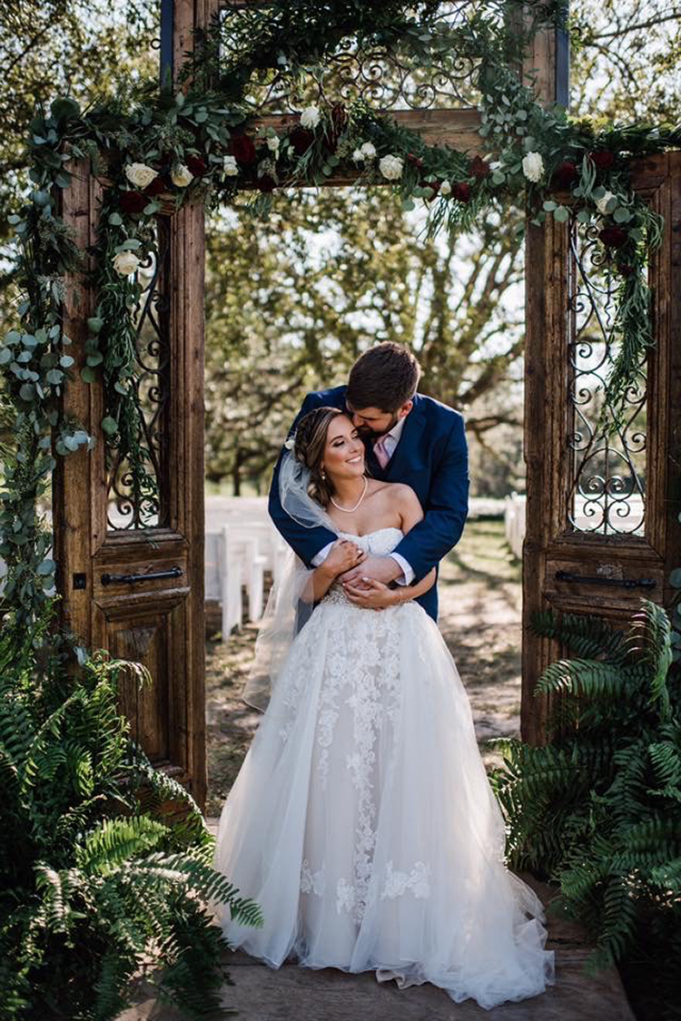 Bride & Groom in front of Wooden Door Wedding Ceremony Decor at The Venue at Southern Oaks | photo by MbM Photography | featured on I Do Y'all