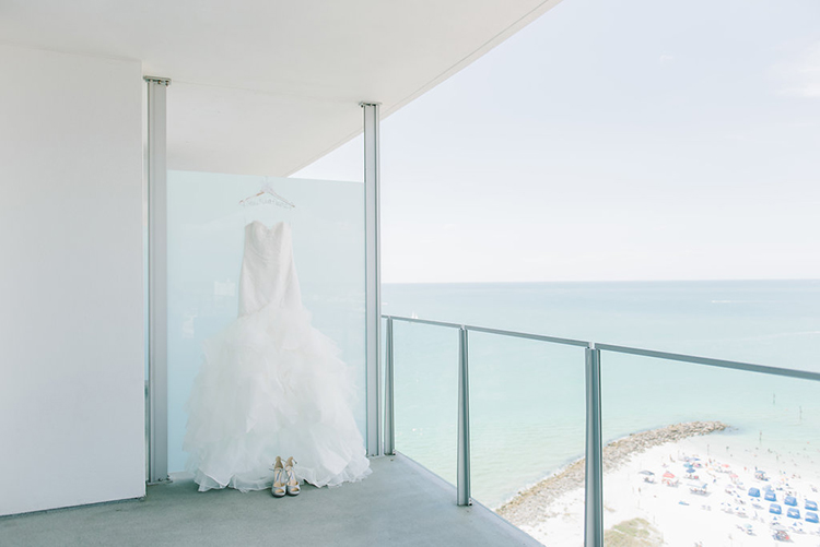 Wedding Dress Hanging on Balcony Overlooking the Ocean | photo by Kera Photography | featured on I Do Y'all for 10 Smart Tips for Long-Distance Wedding Planning
