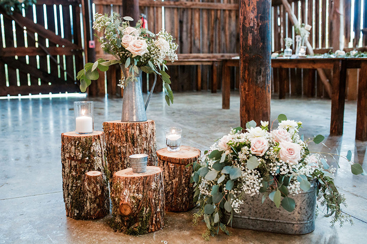 Rustic wedding decor of wood stumps and tin vases | photo by John Myers Photography | featured on I Do Y'all