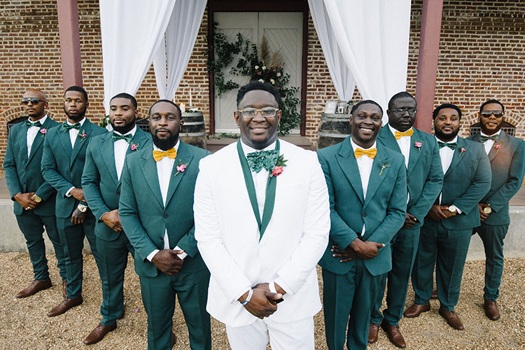 Groom in White Suit & Groomsmen in Emerald Suits with Bowties | photo by Staci Lewis Photography | featured on I Do Y'all