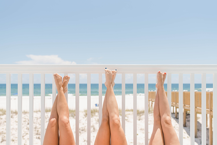 Bridesmaids' Legs Propped up on Wall by Beach | photo by Southern Wedding Pixels | featured on I Do Y'all