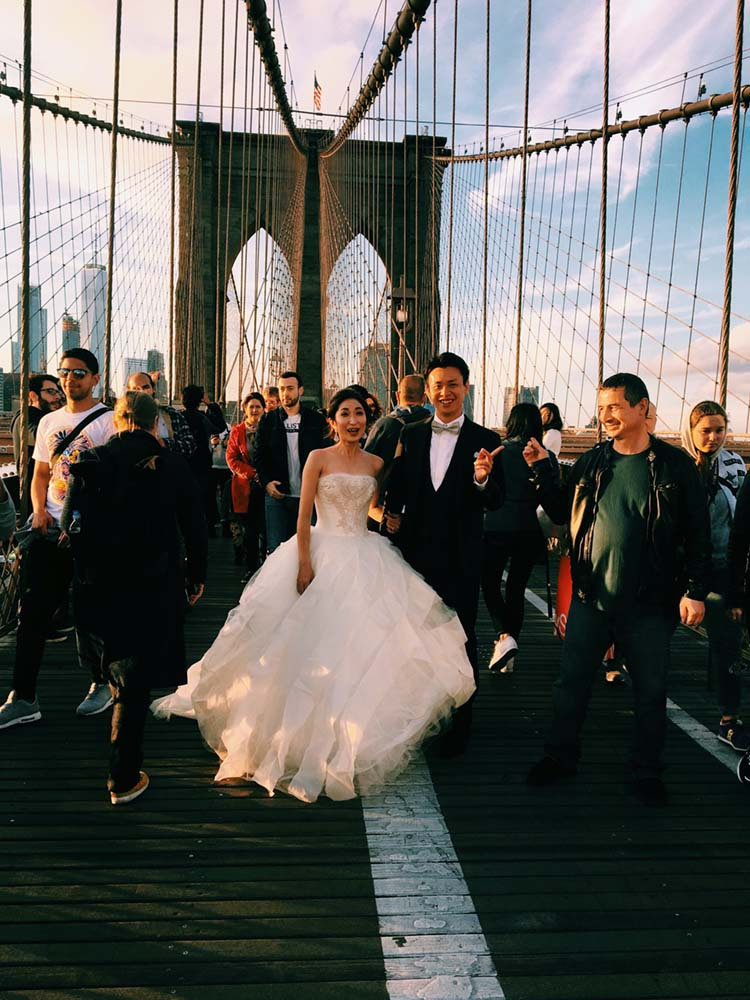Bride & Groom on Brooklyn Bridge Surrounded by People   photo by Eddi Aguirre   featured on I Do Y'all
