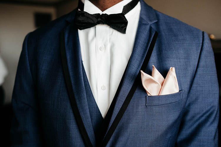 Groom in Blue Suit with Outlined Black Lapels and Black Bowtie | photo by The Portos