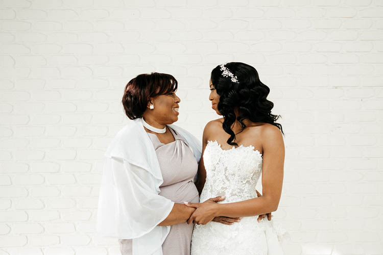 Bride & Mom in Front of White Brick Wall Before Wedding | photo by The Portos