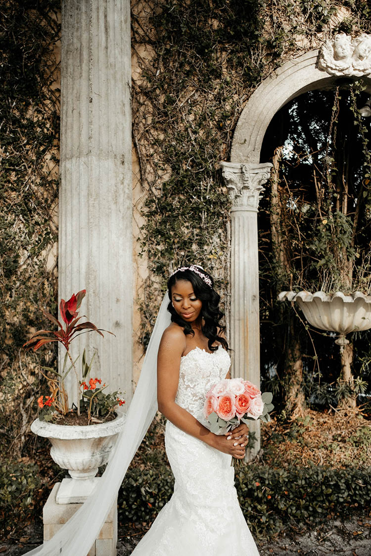 Bride in Fitted Lace Mermaid Style Dress with Illusion Cutouts and Long Veil | photo by The Portos