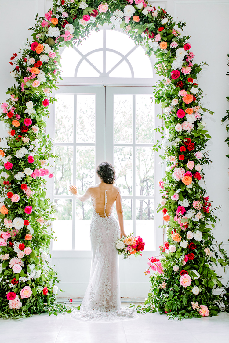 Illusion Back Wedding Dress with Buttons Under Amazing Floral Arch | photo by Gricelda's Photography